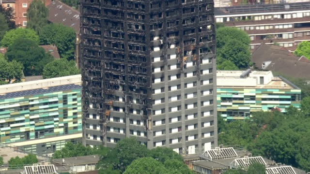 vidéos et rushes de shows aerial shots blackened shell of grenfell tower after fire had been extinguished rising above rooftops of london on 5th july 2017 in london... - 2017