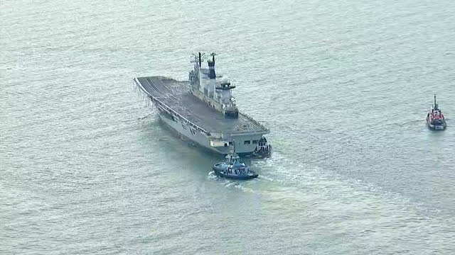 shows aerial shots british navy aircraft carrier hms illustrious being towed away from portsmouth harbour by tug boats britain's last serving... - hms illustrious r06 stock videos and b-roll footage