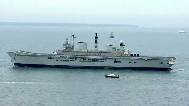 shows aerial shots british navy aircraft carrier hms illustrious being towed away from portsmouth harbour by tug boats pan from tug boat to side view... - hms illustrious r06 stock videos and b-roll footage