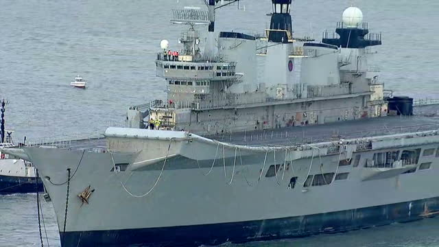 shows aerial shots british navy aircraft carrier hms illustrious being towed away from portsmouth harbour by tug boats with people standing on the... - hms illustrious r06 stock videos and b-roll footage