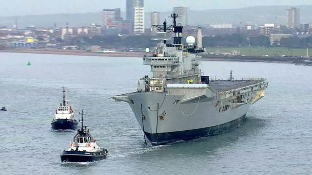 shows aerial shots british navy aircraft carrier hms illustrious being towed away from portsmouth harbour by tug boats pan out from people on bridge... - hms illustrious r06 stock videos and b-roll footage