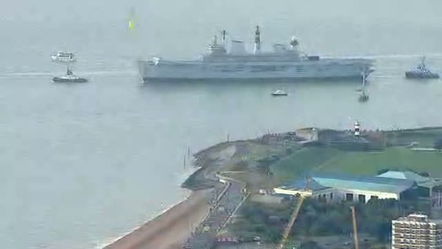 shows aerial shots british navy aircraft carrier hms illustrious being towed away from portsmouth harbour by tug boats with portsmouth's spinnaker... - hms illustrious r06 stock videos and b-roll footage