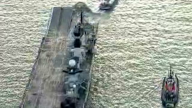 shows aerial shots british navy aircraft carrier hms illustrious being towed away from portsmouth harbour by tug boats with close up people standing... - hms illustrious r06 stock videos and b-roll footage