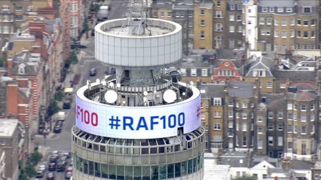 vídeos de stock e filmes b-roll de shows aerial shots bt tower displaying message celebrating 100 years of the raf the queen and senior royals have been helping the royal air force to... - bt tower londres