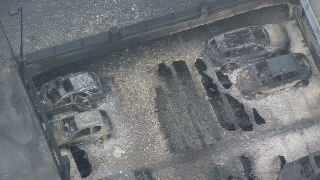 Shows aerial shots burnt out shells of melted cars parked on roof of multistorey car park and damage to building structure caused by intense heat of...
