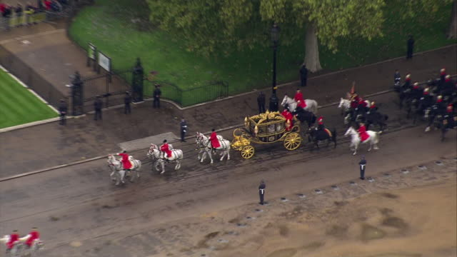 shows aerial shots carriage containing queen elizabeth ii, camilla duchess of cornwall and prince charles prince of wales driving across horse guards... - autumn stock videos & royalty-free footage