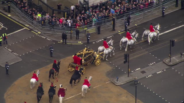 shows aerial shots carriage containing queen elizabeth ii, camilla duchess of cornwall and prince charles prince of wales driving along whitehall,... - cocchio video stock e b–roll
