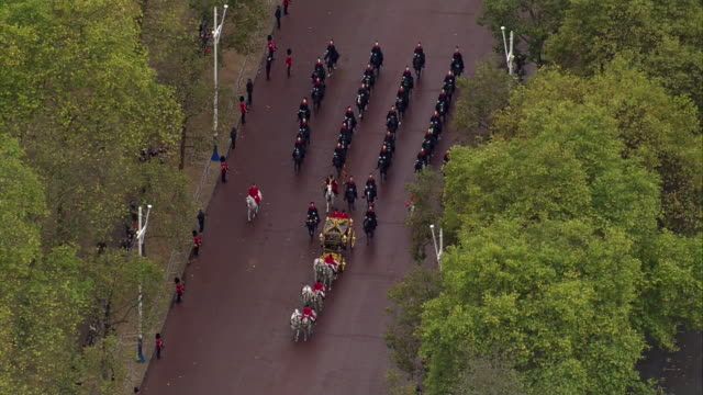 shows aerial shots carriage containing queen elizabeth ii, camilla duchess of cornwall and prince charles prince of wales heading along the mall... - the queen's speech state opening of uk parliament stock videos & royalty-free footage
