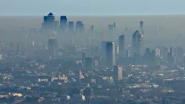 Shows aerial shots cloud of smog and pollution rising above Central London with towers of buildings at Canary Wharf poking through High pollution...