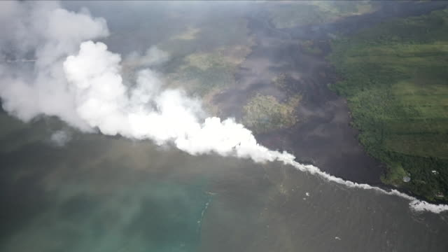 Shows aerial shots clouds of steam rising from the point lava from the Kilauea volcano reaches the Pacific Ocean lava flows across the landscape and...