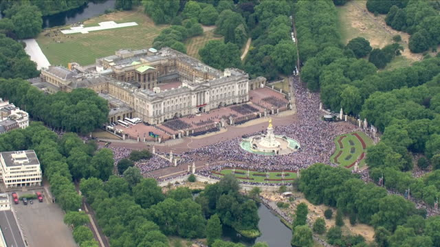 vídeos de stock e filmes b-roll de shows aerial shots crowds gathered in front of buckingham palace and along the mall waiting for the raf 100 flypast to start the queen and senior... - centenário