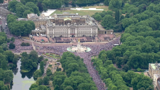 shows aerial shots crowds gathered near admiralty arch along the mall and in front of buckingham palace waiting for the raf 100 flypast to start the... - 英国空軍点の映像素材/bロール
