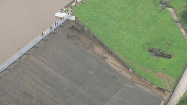 shows aerial shots damage to dam at toddbrook reservoir with people working to shore it up and prevent further breaches or collapse. it's survived... - derbyshire stock-videos und b-roll-filmmaterial