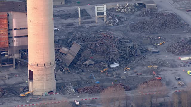 shows aerial shots didcot power station building collapse with zoom in to pile of rubble with construction vehicles next to it one person has been... - didcot stock videos and b-roll footage