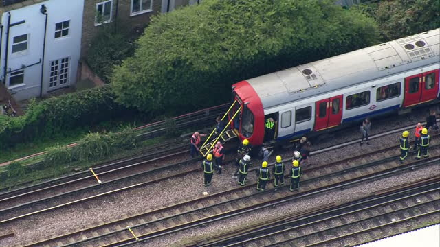 Shows aerial shots emergency serivces at scene of attack passengers being helped off train and along tracks to safety and forensics officers carrying...