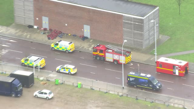 Shows aerial shots equipment and supplies from emergency services laid out on pavement with pans across emergency vehicles parked in roads around...