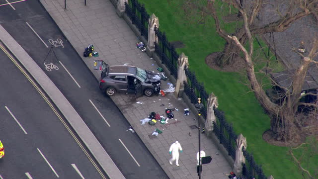 Shows aerial shots forensics officers at crime scene working near car crashed into the railings around New Palace Yard Westminster Palace following...