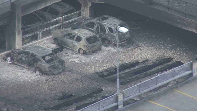 Shows aerial shots melted and burnt out shells of cars and intense fire damage to car park caused by heat of fire in multistorey car park More than a...
