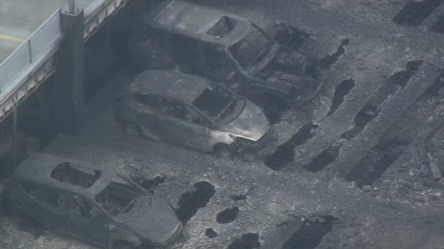 Shows aerial shots melted and burnt out shells of destroyed cars on roof of multistorey car park intense fire damage and holes in concrete flood of...
