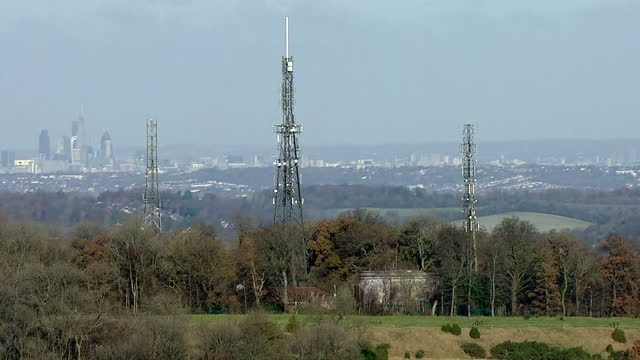 Shows aerial shots mobile telecoms tower on hilltop with pan to skyscrapers in Central London on November 28 2016 in London England