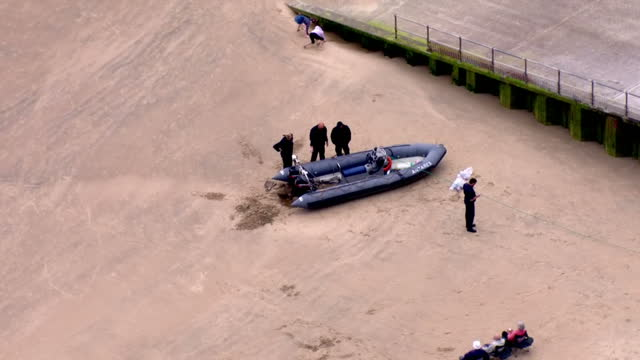 shows aerial shots officials inspecting rubber dinghy migrants rescued from on beach at dymchurch kent exterior shots dymchurch beach and coastguard... - イングランド ケント点の映像素材/bロール