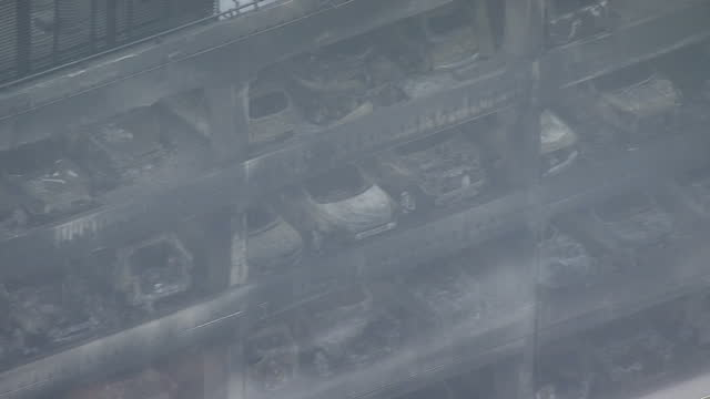 Shows aerial shots pan along side of multistorey car park showing black smoke damage to building structure and damaged cars still parked across...