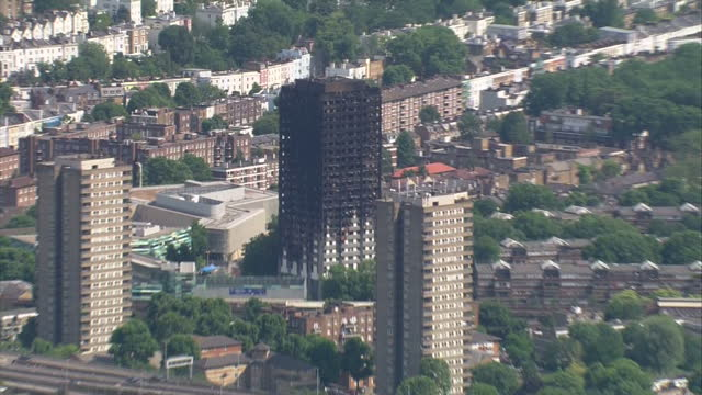 shows aerial shots pan from burnt out remains of grenfell tower to westway sports and fitness centre where some of the survivors were offered... - co ordination stock videos & royalty-free footage