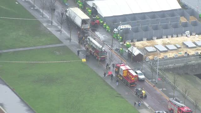 Shows aerial shots pan from fire damaged car park with burnt out melted cars on roof to fire engines and firefighters in surrounding roads More than...