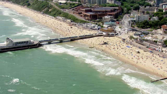 stockvideo's en b-roll-footage met shows aerial shots pan into, along and out from people having fun on beach at bournemouth, on a sunny summer's day on 28th june, 2019 in england,... - het kanaal
