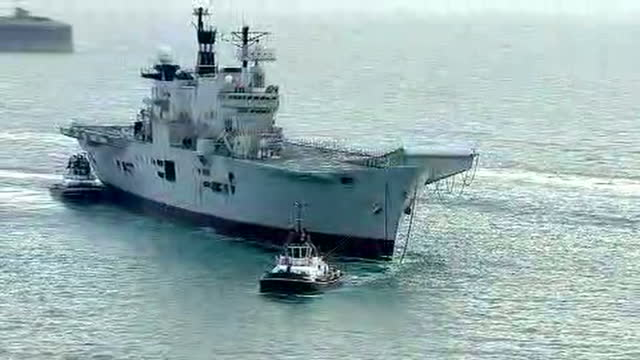 shows aerial shots pan round british navy aircraft carrier hms illustrious being towed away from portsmouth harbour by tug boats britain's last... - hms illustrious r06 stock videos and b-roll footage