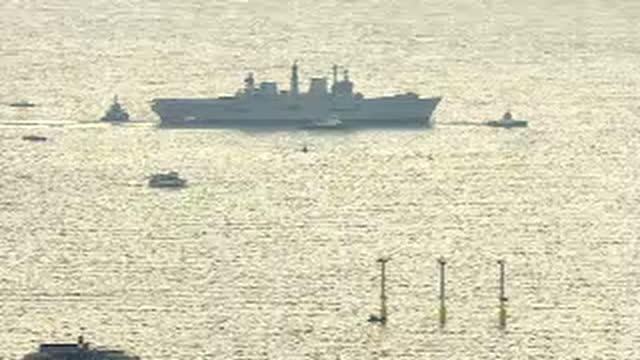 shows aerial shots portsmouth spinnaker tower with pan to british navy aircraft carrier hms illustrious being towed away from portsmouth harbour by... - hms illustrious r06 stock videos and b-roll footage