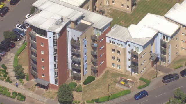 shows aerial shots residential area in west london showing blacks of apartments. a report into covid-19 among black, asian and ethnic minority people... - flat stock videos & royalty-free footage