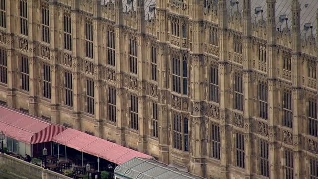 Shows aerial shots Ricer side of The Houses of Parliament Palace of Westminster including close up of River Terrace and pan up Victoria Tower to flag...