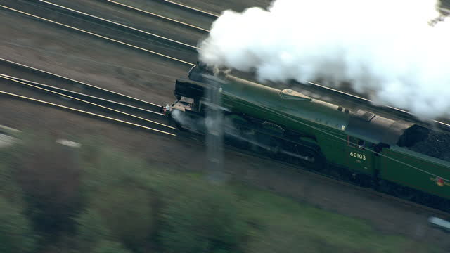Shows aerial shots The Flying Scotsman Steam Locomotive coming out of tunnel and passing under bridges as it travels through North London past the...