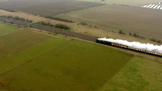 Shows aerial shots The Flying Scotsman Steam Locomotive travelling through rural fields with line of smoke behind it The Flying Scotsman's inaugural...