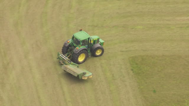 shows aerial shots tractor cutting grass in field on farm the governor of the bank of england warned today of the triple threat of slow growth... - grass stock videos & royalty-free footage