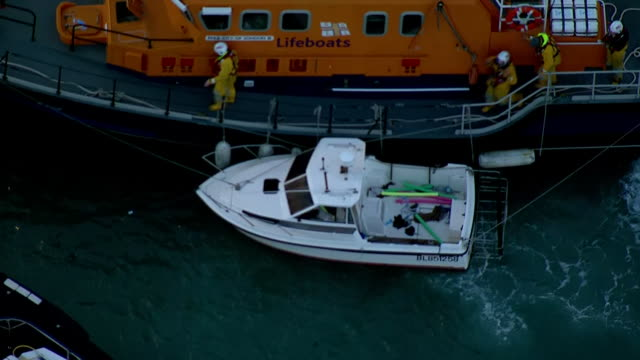 shows aerial shots uk lifeboat with smaller boat tied alongside in which migrants tried to cross the english channel moored in dover harbour with... - english channel stock videos & royalty-free footage