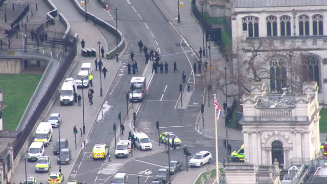 shows aerial shots wide shot including westminster bridge and houses of parliament with pan into emergency services vehicles filling road in... - westminster bridge stock-videos und b-roll-filmmaterial