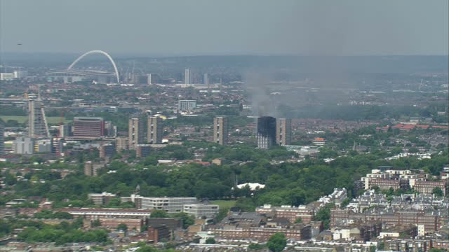 shows aerial shots zoom into grenfell tower block in west london with smoke blackened top and smoke rising from remains as fire crews aim water hoses... - stockwerk stock-videos und b-roll-filmmaterial