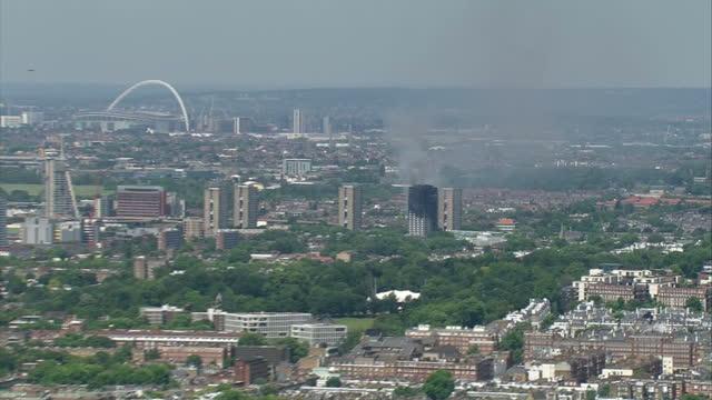 vídeos y material grabado en eventos de stock de shows aerial shots zoom into grenfell tower block in west london, with smoke blackened top and smoke rising from remains as fire crews aim water... - piso de edificio