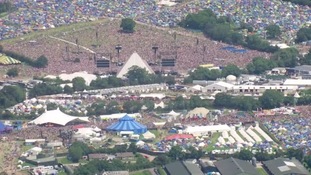 vidéos et rushes de shows aerial wide shots glastonbury music festival focusing in on the pyramid stage with tents and performance areas spread across fields. ever since... - audience de festival