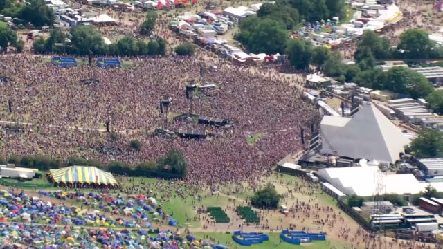 shows aerial wide shots glastonbury music festival pan from crowds at the pyramid stage to colourful tents in field ever since the heady days of... - crowd stock videos & royalty-free footage
