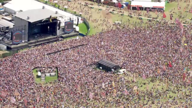 shows aerial wide shots glastonbury music festival with crowd of people watching performance on the other stage. ever since the heady days of... - spectator stock videos & royalty-free footage