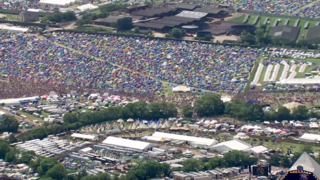 vidéos et rushes de shows aerial wide shots glastonbury music festival with people walking between tents and crowd watching show on pyramid stage. ever since the heady... - audience de festival