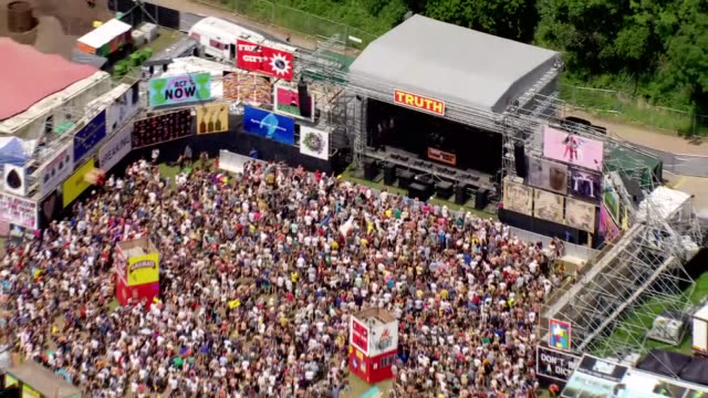 vidéos et rushes de shows aerial wide shots glastonbury music festival with people watching the truth stage. ever since the heady days of woodstock, music and political... - audience de festival