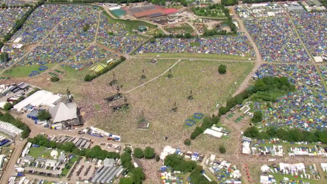 vidéos et rushes de shows aerial wide shots glastonbury music pan out from crowds outside the pyramid stage. ever since the heady days of woodstock, music and political... - audience de festival