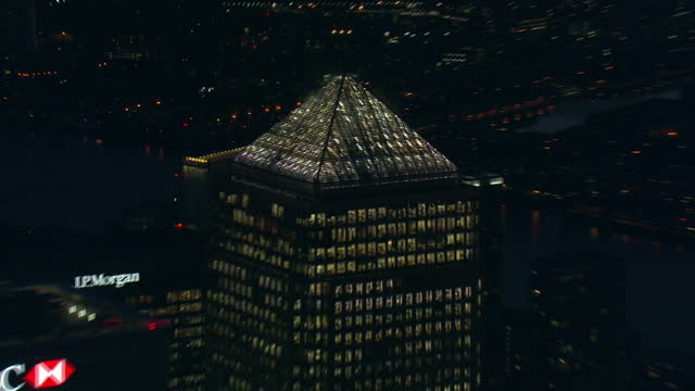 vídeos de stock e filmes b-roll de shows aerials across london skyline at night with lights on in many buildings including tower bridge and financial district around canary wharf with... - hsbc towers