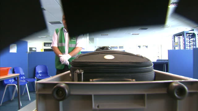 shows camera passing through airport security luggage x-ray scanner along conveyor belt on november 12, 2015 in doncaster, england. - security staff stock videos & royalty-free footage