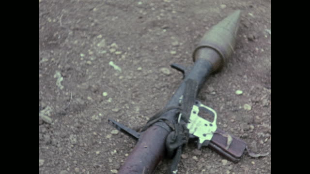 shows dead north vietnamese sappers/commandos and weapons including hand grenades explosive charges and a rocket propelled grenade still attached to... - ベトコン点の映像素材/bロール