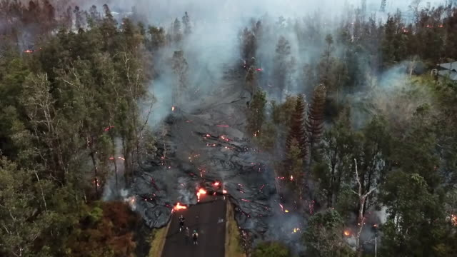 vídeos de stock, filmes e b-roll de shows drone aerial shots lava spreading across road, swallowing up trees in neighbourhood near mount kilaueu. lava from the kilauea volcano erupting... - 2018